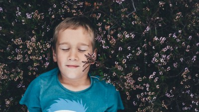 A child lays in the grass and practices mindfulness exercises
