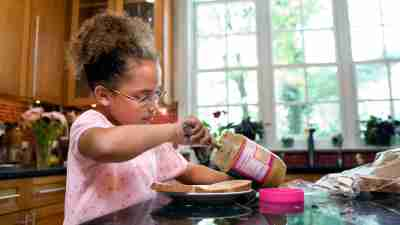 A young girl with ADHD making herself a peanut butter sandwich to manage her increased appetite