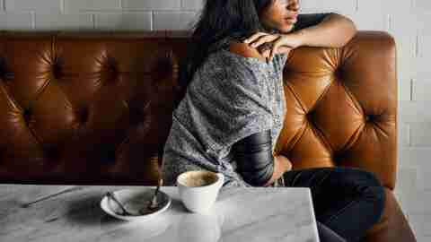 A lonely woman with ADHD sits alone in a coffee shop.