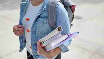 A woman with undiagnosed ADHD walks to her college class with books in hand.