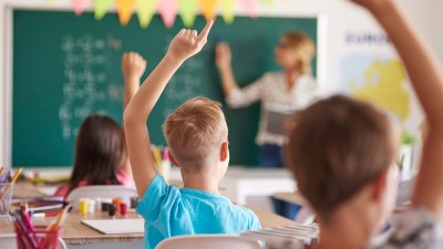 A teacher stands at the front of the class telling students about ADHD success stories