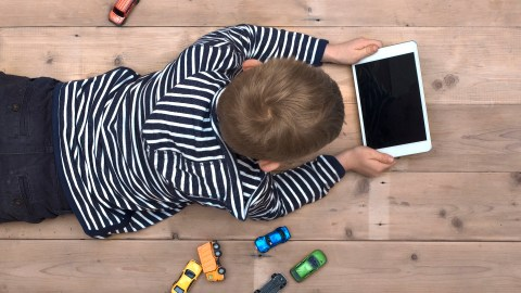 A boy with ADHD plays with a tablet instead of cars