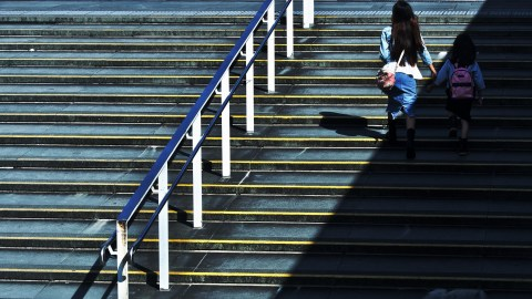 A mom with ADHD walks up stairs with her daughter