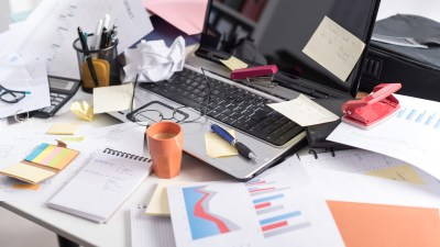 A cluttered desk in a home office that is difficult to clean