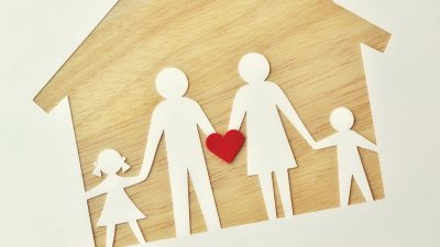 A paper family on a wooden house, holding a heart to represent love, support, and ADHD help