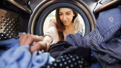 A woman with ADHD doing laundry as a form of procrastination