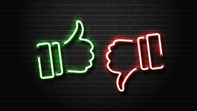 "Neon thumbs up and thumbs down sign, similar to social media ""like"" buttons; social media can make people feel bad"