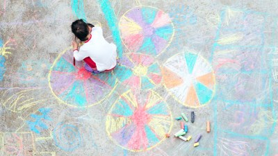 A young girl with ADHD making friends on the playground by drawing chalk illustrations
