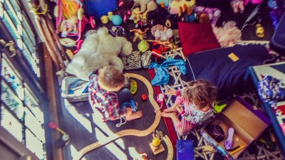 Two kids clean up a playroom with toys everywhere