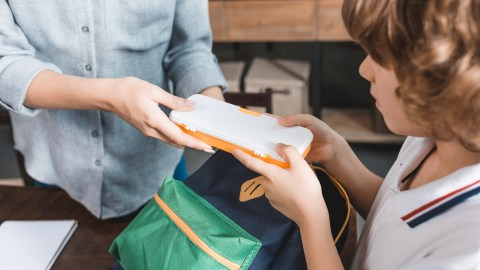 An ADHD is prepared, and helps her child with ADHD pack his backpack with supplies.