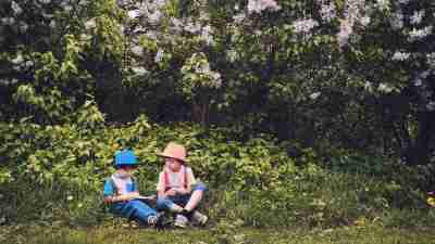 Two boys read outside to avoid the summer slide.