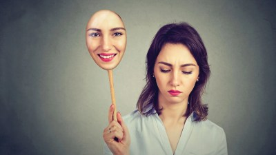 A woman with ADHD and BPD holding a mask of her happy face, looking down sadly