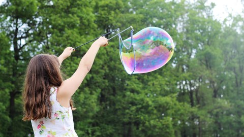 A girl plays with bubbles outside as part of her nature therapy for ADHD