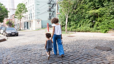 A mom walks outside with her daughter in a city as part of her nature therapy regimen.