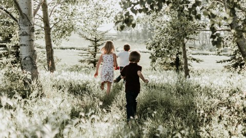 Three kids run outside as part of their nature therapy for ADHD
