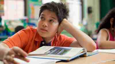 A boy with attention problems, who is easily distractible daydreams in class.