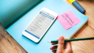A parent with ADHD uses her phone and a calendar to manage self-care and organization.