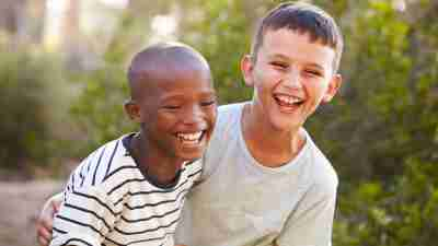 Two impulsive children embrace and laugh outside.