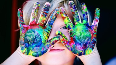 A child diagnosed as neurodiverse paints with his hands.