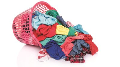 Clothes spilling out of a basket, symbolizing the challenges of doing laundry with ADHD