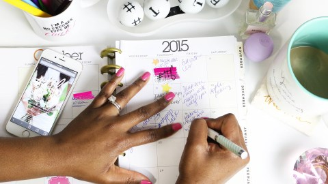 Woman using a planner calendar to organize her ADHD life