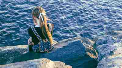 Little girl facing away from the camera and looking toward the water, symbolizing ADHD and emotional withdrawal in women
