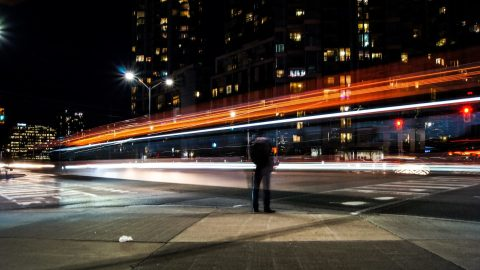 long exposure of headlights passing a stationary man, representing an adhd couple where one partner has hyperfocus