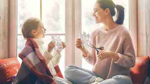 A mom makes snowflakes with her daughter after prioritizing during the holidays