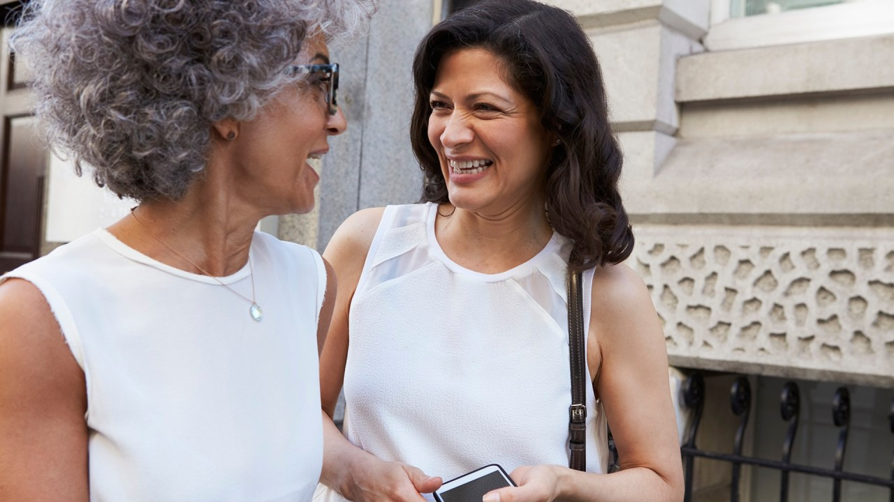 Two women talk after making friends as adults.