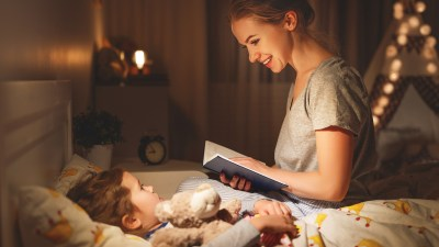 A mother reads books about understanding ADHD to her daughter before bed.