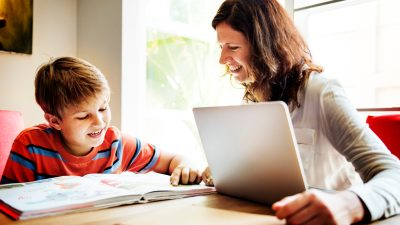Son doing homework with mom