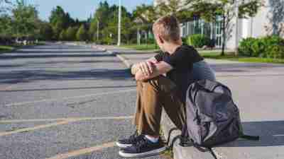 The image displays a lonely teenage boy sitting on the curb in front of his high school at the end of the school day.