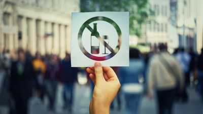 Hand holding a paper sheet with no alcohol sign over a crowded street background. Stop to drink symbol prohibited icon. Refuse to be dependent.