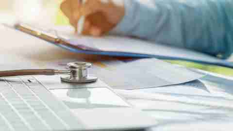 Doctor working in hospital writing prescription clipboard, working an Laptop on desk in hospital with report analysis, Healthcare and medical concept, selective focus