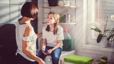 Daughter sitting on washing machine by the window using smart phone and talking with mother