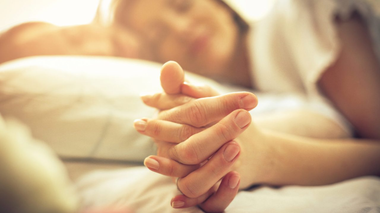 A heterosexual couple holding hands in bed.The key to a better relationship? Better sex, according to a new ADHD couples survey.