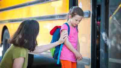 Anxiety in Children with ADHD: A young girl with shoulder hunched appears shy to enter the school bus as her mother comfort her by touching her arm