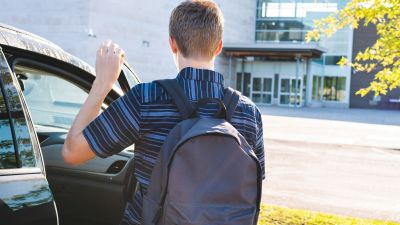 A male teenager exiting his car as he arrives at school in the morning to illustrate skipping school.