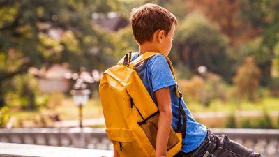 School boy wearing backpack sitting alone
