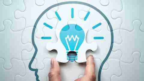 Hand completing puzzle of brain with lightbulb, signifying ingenious brain hacks and productivity secrets
