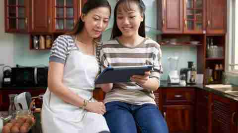 Smiling Vietnamese mother and daughter reading recipe of new dish on tablet computer