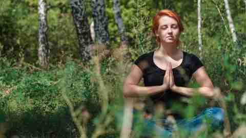 Young beautiful ginger girl in black t-shirt meditates in summer birch forest. Tranquility and concentration concept with copy space.