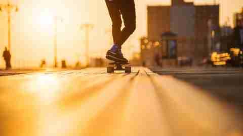 Young teenage couple riding longboards on boardwalk Coney Island, New York, having fun,