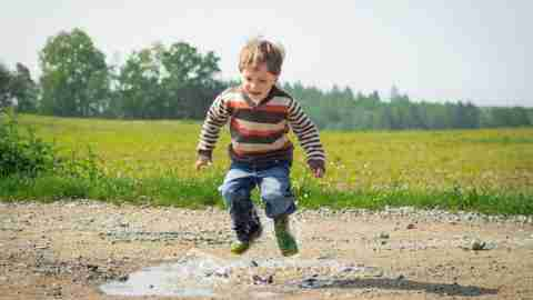 Boy with ADHD jumping in a mud puddle