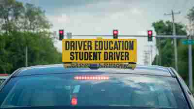 Drivers ed sign on car roof at stoplight in daylight