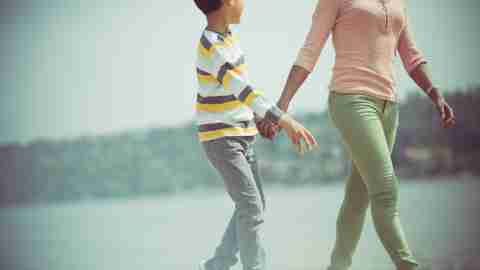 Mother and young son holding hands while walking
