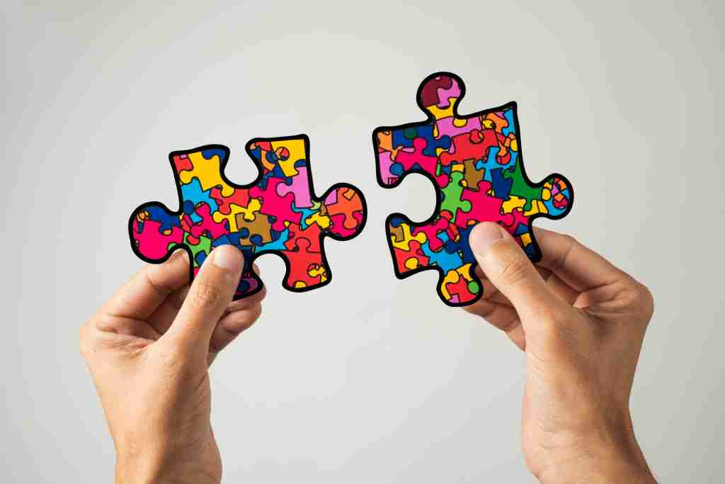 closeup of a man with two puzzle pieces patterned with many puzzle pieces of different colors, symbol of the autism awareness, on a white background