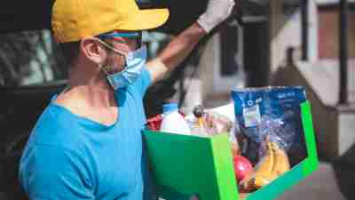 autism resources - a man carrying groceries while wearing a face mask and gloves