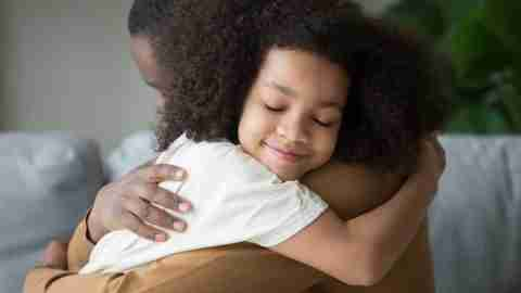 Emotional regulation: A young child hugging her father with a smile on her face.
