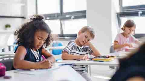 A small tired school boy sitting at the desk in classroom, sleeping. He may need a functional behavior assessment and behavior plan.